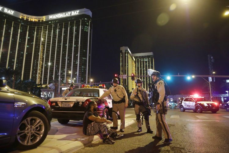 Police officers stand at the scene of a shooting near the Mandalay Bay resort and casino on the Las Vegas Strip, Sunday, Oct. 1, 2017, in Las Vegas. Multiple victims were being transported to hospitals after a shooting late Sunday at a music festival on the Las Vegas Strip.  (AP Photo/John Locher)