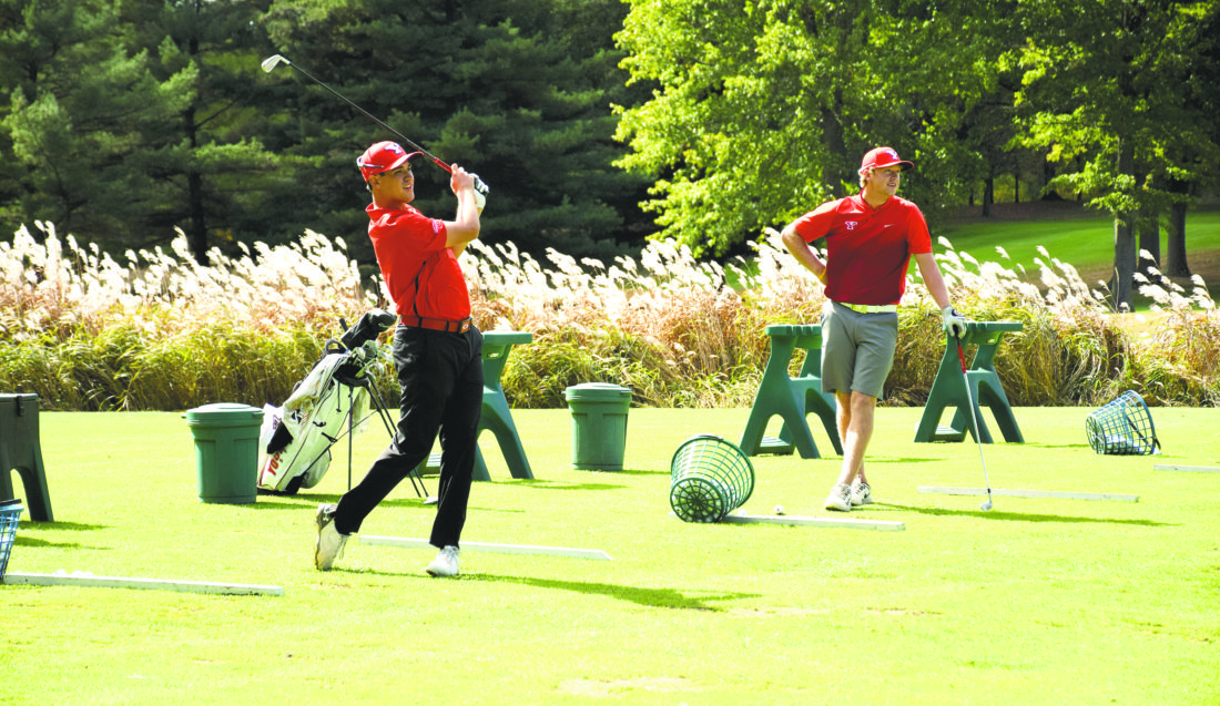 Tribune Chronicle / John Vargo Justin Hallapy, a Hubbard High School graduate, follows through with an iron on the driving range as teammate Justin Stark looks on. Hallapy is one of five local golfers on the Youngstown State University men's golf roster.