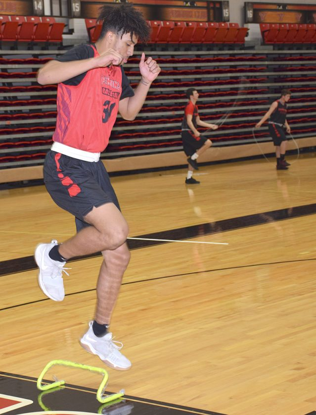 Tribune Chronicle / John Vargo YSU's Michael Akuchie works on an agility drill as teammates jump rope in the background.