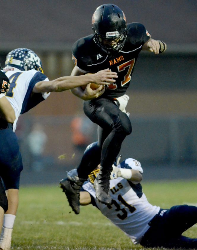 Tribune Chronicle / R. Michael Semple Dakota Edwards (17) of Mineral Ridge leaps over McDonald defender Alex Cintron (31) during the Blue Devils' 48-6 win over the Rams Friday night at Mineral Ridge.