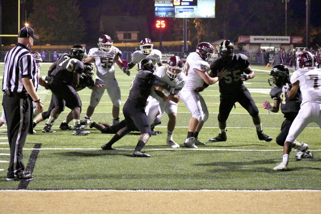 Tribune Chronicle / Marc Weems Boardman quarterback Michael O'Horo, middle, tries to break the tackle of Warren G. Harding's Jeremy Wilson, left, during the Spartans' 28-21 victory Friday at Mollenkopf Stadium in Warren.