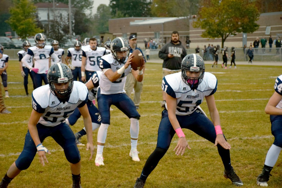 Tribune Chronicle / John Vargo Grand Valley's Michael McGovern (2) catches the snap from center Ryan Busser (51) while teammate Burt Miller (55) prepares to block during warm-ups prior to their game against Windham. The Mustangs won, 28-17.