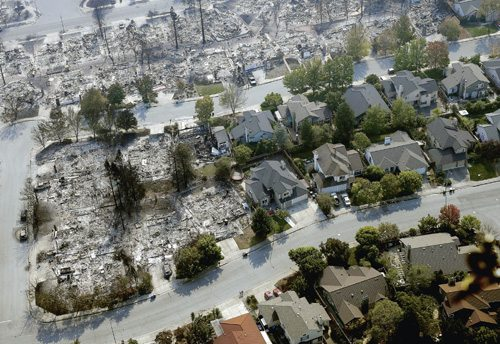 AP Burned out homes are seen next to homes that survived the flames of a massive wildfire in the Coffey Park area Wednesday in Santa Rosa, Calif. Wildfires whipped by powerful winds swept through Northern California forcing residents to leave through smoke and flames as homes burned.