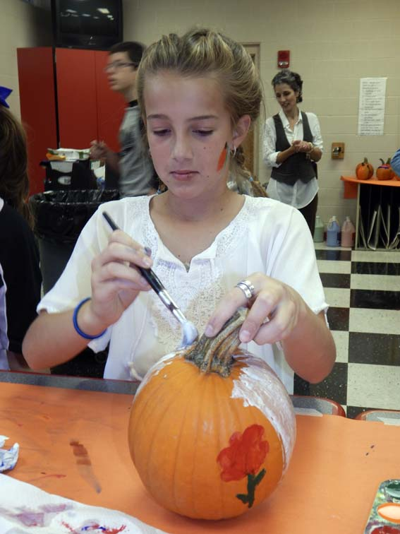 Tribune Chronicle / Bob Coupland Elizabeth Rossi, 10, a fifth-grader, paints a pumpkin Tuesday at the Niles Middle School annual fall festival.