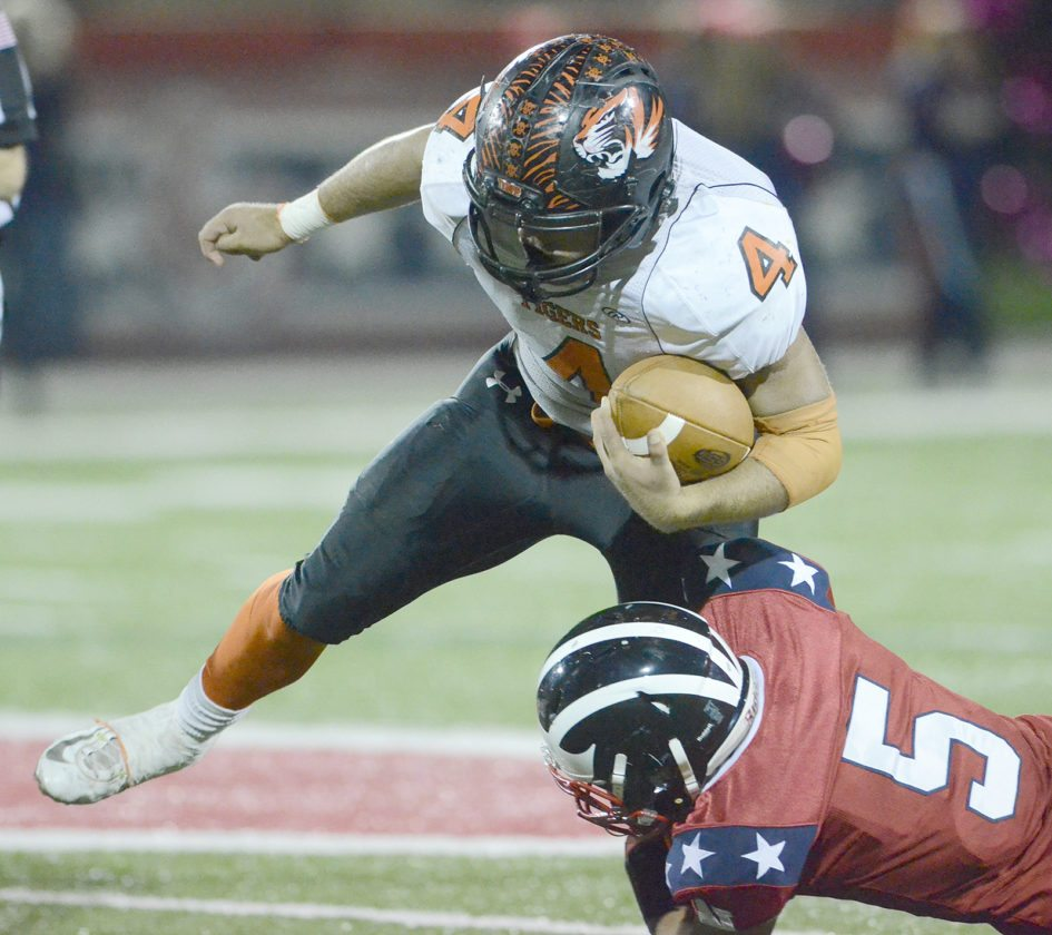 Jackson Deemer (4) of Howland tries to escape the tackle of Niles' Seth McMillion (5) Thursday night during the Tigers' 42-3 victory over the Red Dragons at Bo Rein Stadium in Niles. Deemer scored three touchdowns and ran for 226 yards in the victory.