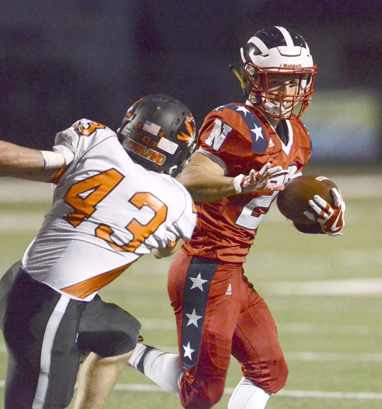 Niles' #28 Robbie Savin rushes for yardage as Howland's #43 Justin Gray pursues during 1st Qt. action...by R. Michael Semple