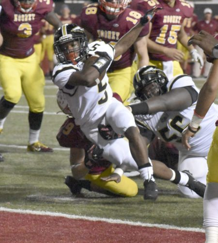 Tribune Chronicle / Marc Weems Warren G. Harding's Geivanni Washington (5) dives into the end zone as teammate Simahjay Warfield blocks Friday at Stambaugh Stadiium in Youngstown where the Raiders lost, 15-14, to Cardinal Mooney.