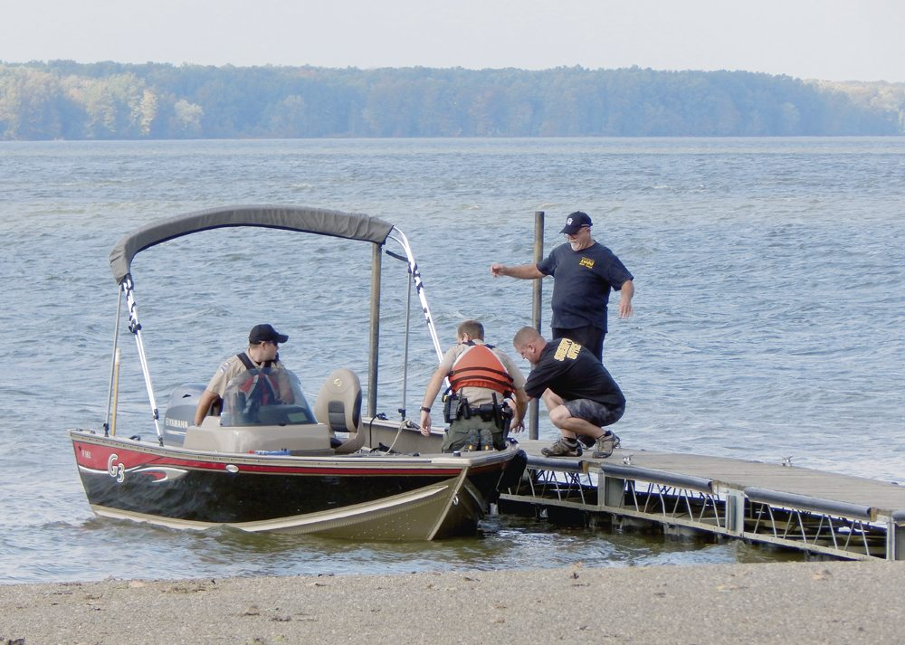 Tribune Chronicle photos / Bob Coupland Members of the Ohio Department of Natural Resources Division of Parks and Watercraft, with assistance from Bazetta Fire Department, prepare to search Mosquito Lake in a boat for John Schuster, 51, who fell out of a canoe Sunday morning while fishing with another man.