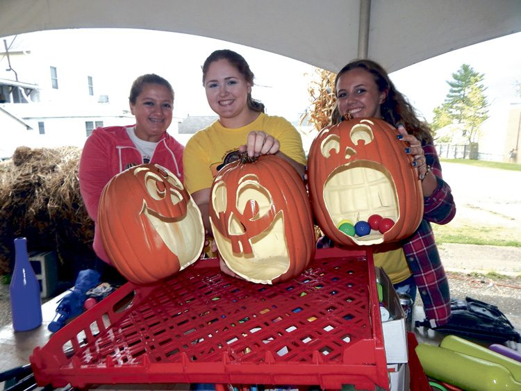 Cortland residents, from left, Shelby Nichols,  Megan Cross and Caitlyn Dales were among several who donated time putting up Halloween and fall decorations for the two-day Cortland Oktoberfest on Main Street.