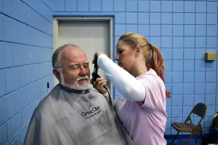 Missy Sutton cuts Ken David's hair.