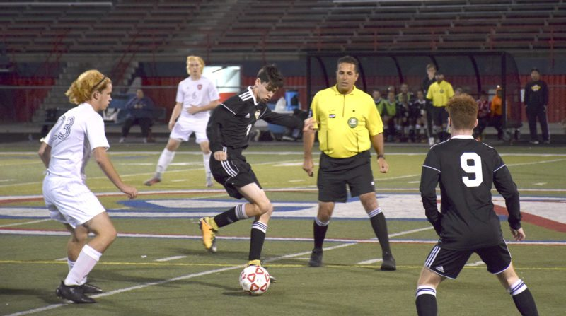 Tribune Chronicle / John Vargo Warren G. Harding's Thomas Malacky dribbles in midfield as Austintown Fitch's Zack Glavic, left, closes in during their Division I sectional tournament game Wednesday night on the Falcons' field. Fitch won the game, 4-1.