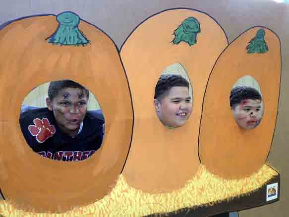 Tribune Chronicle / Bob Coupland From left, Frank Hunter, 10, Emmanuel Washington, 13, and Freddy Washington, 13, all of Warren, get their photos taken Thursday at the Warren Family Mission's harvest party  for families. The event, which was sponsored by Novelis, included games, pumpkin decorating and food. There was also an aluminum can collection.