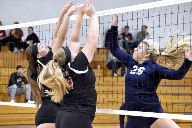 Tribune Chronicle / Marc Weems Mathews' Sadie Bertok, left, and Chloe Howdershelt  try to block the shot of Brookfield's Olivia Vogel during their Division IV sectional matchup at Lakeview High School on Thursday. Mathews advanced with a 3-1 victory over the Warriors.