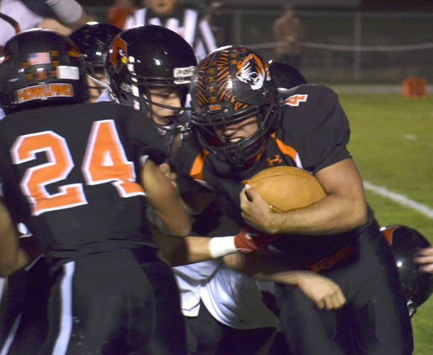 Tribune Chronicle / John Vargo Howland's Jackson Deemer (4) fights for yardage as teammate Michael Wilson (24) blocks during the Tigers' 31-10 loss at home Friday night against Canfield.