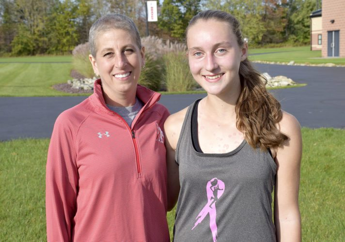 Tribune Chronicle / John Vargo Badger girls cross country coach Carrie Albert, left, poses with sophomore runner Miranda Stanhope. Albert continues to coach her team while battling breast cancer.