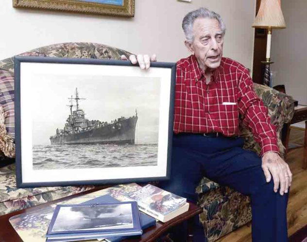 Tribune Chronicle / R. Michael Semple U.S. Navy veteran Michael Salcone, 93, of Warren shows a photo of the ship he served on during World War II.
