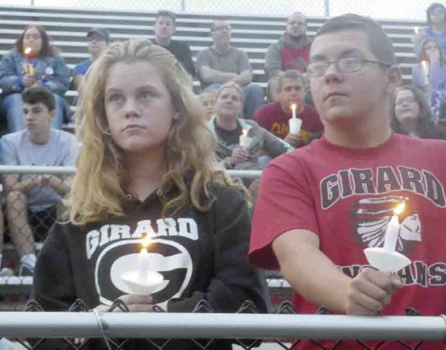 Tribune Chronicle / Guy Vogrin Viola McClimans, left, a freshman at Girard High School, and Hunter Patrick, attend a vigil Sunday evening for Girard police officer Justin Leo, 31, who was shot and killed Saturday night.
