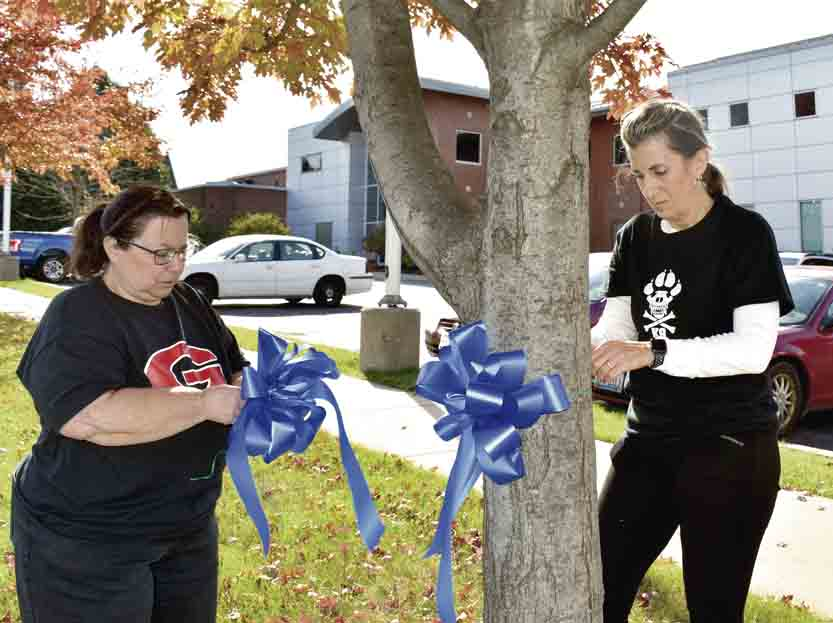 Tribune Chronicle / Renee Fox Lisa Manente and Patricia DelGenio tie blue ribbons to the trees Sunday outside the Girard Police Department to honor Girard police officer Justin Leo, 31, who was shot and killed Saturday night. Leo and another police officer responded to 408 Indiana Ave. for a domestic violence call. Leo died just before midnight in surgery at St. Elizabeth Youngstown Hospital. Both women said they are connected to law enforcement through their families and felt the need to do something after learning about Leo's death.