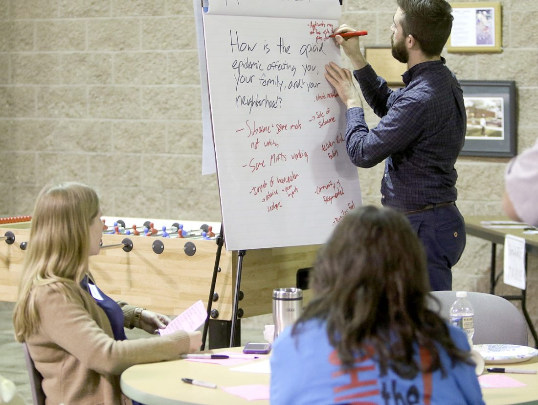 Special to the Tribune Chronicle Andrew Rockway writes down answers from the round tables at the Your Voice Mahoning Valley meeting Sunday at the Boys & Girls Club in Youngstown.