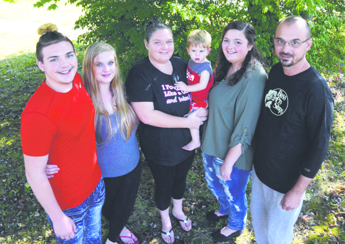 Tribune Chronicle / R. Michael Semple From left, son Michael Kellar, daughter Kourtnie Lichty, mom Angela Kellar — holding grandson Dylan Maras, 15 months — daughter Ariel Kellar and husband Mike Kellar gather for a family portrait. Angela Kellar said family support was vital in her battle against cancer.