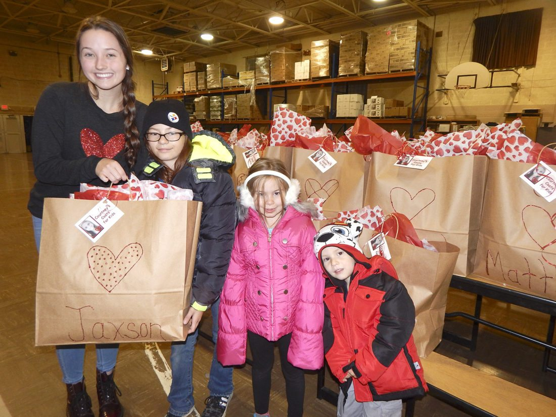 Tribune Chronicle / Bob Coupland Gabriella Miller of Niles, left, hands out bags of winter coats to Paige Dirando, 11, Skylar Lewis, 6, and Jaxson Lewis, 4, at the Courtney's Coats for Kids program in Niles in which local children get winter coats. The program was started by the Lisa and Bob Miller family in memory of their daughter, Courtney, who was a Niles graduate and died shortly before she was to graduate from the Ohio State University.