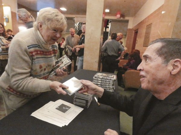 Tribune Chronicle/Andy Gray Roy Firestone, right, signs a CD for Jackie Bremick of Howland during intermission of his Warren Civic Music Association concert at Packard Music Hall.