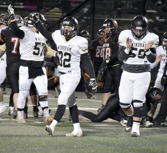 Tribune Chronicle / Marc Weems Windham's Hunter Shackelford (32) celebrates with fellow defenders Calvin Harvey (57) and James Harvey (59) after the Bombers stopped Dalton on fourth down Friday at North Canton Hoover in a regional semifinal.