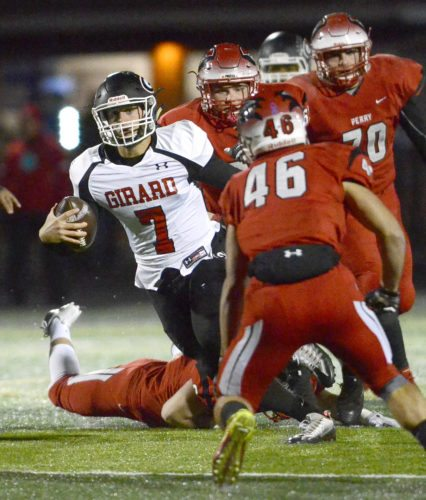 Tribune Chronicle / R. Michael Semple Girard quarterback Mark Waid (7) looks for running room against a host of Perry defenders Friday night at Twinsburg in a Division IV regional semifinal. Perry beat the Indians, 50-21.