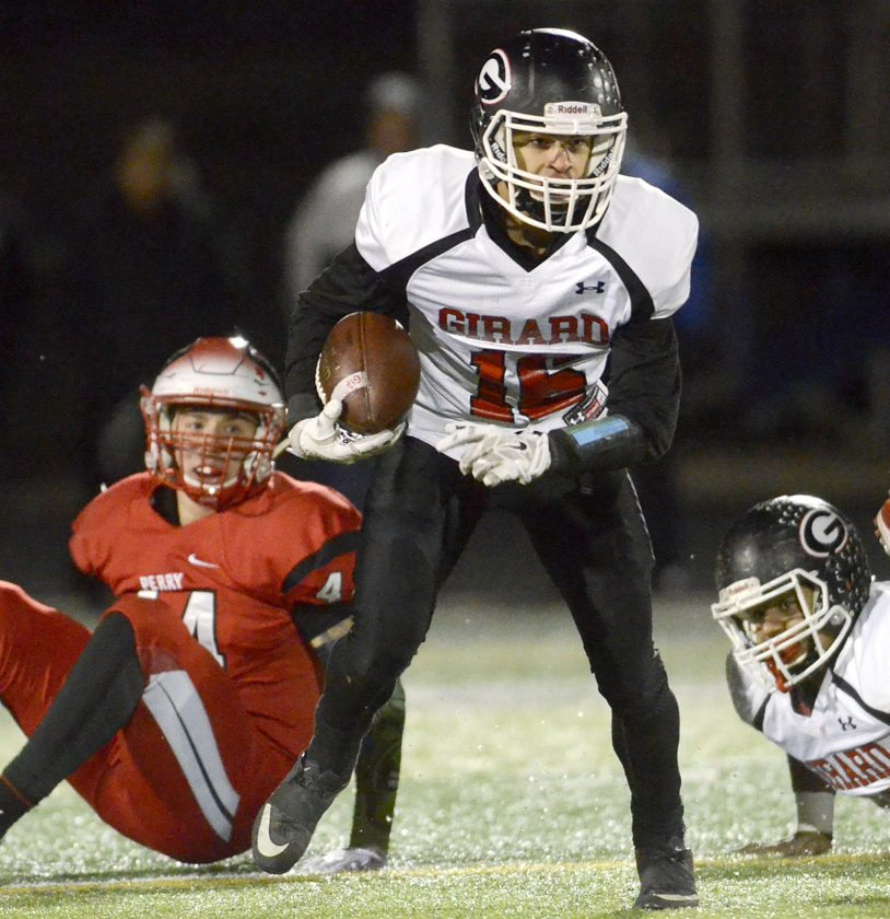 Tribune Chronicle / R. Michael Semple Morgan Clardy looks for running room after getting away from Perry's Cody Baranauskas, left. The Pirates beat the Indians, 50-21, in the Division IVregional semifinal.