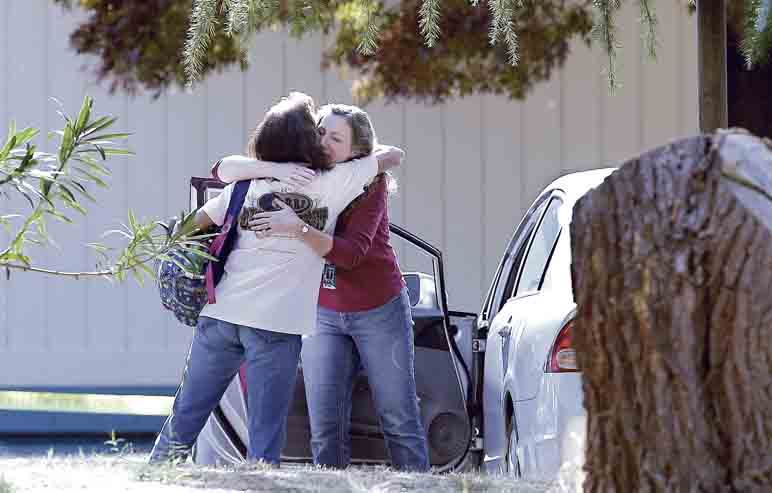 AP Two women embrace outside Rancho Tehama Elementary School, where a gunman opened fire Tuesday in Corning, Calif. Authorities said a gunman choosing targets at random opened fire in a rural Northern California town, killing four people at several sites and wounding others at qn elementary school before police shot him dead.
