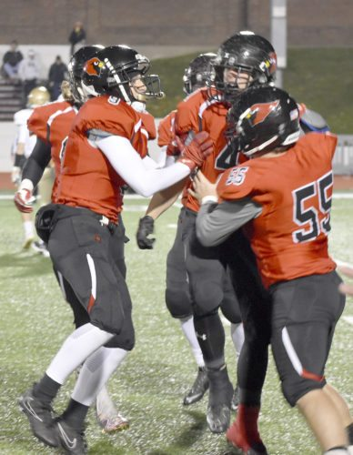 Tribune Chronicle / Joe Simon Canfield's Anthony D'Alesio (41) is greeted by teammates Vince Giordano (55) and Nick Ieraci after D'Alesio blocked a punt Friday night in the Cardinals' 13-10 loss to Akron St. Vincent-St. Mary in a Division III regional final at Salem.