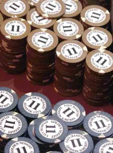 AP Gambling chips sit on table game inside a casino.