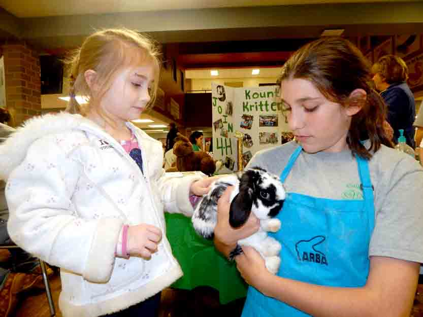 Tribune Chronicle / Bob Coupland Madison Brainard, 11, of Hubbard and a member of the Kounty Kritters 4H Group, right, shows off ''Oreo'' to Eliza Schrock, 7, of North Bloomfield, at the fourth annual 4H Night held at Trumbull Career and Technical Center and sponsored by the Trumbull County 4-H Advisory Committee.