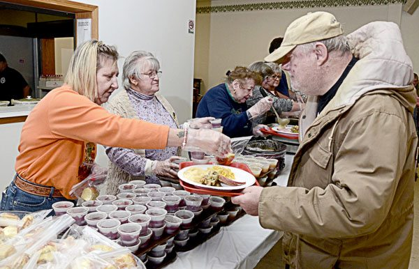 112117...R BROOK DIN 4...Brookfield...11-21-17...Volunteers Tammy Pipic of Brookfield, left, and Cora Baxter of Brookfield, center, serve Tom Wojnar of Vienna, right, during the 8th annual Brookfield Community Thanksgiving dinner Tuesday afternoon at the fire dept. hall...Approx 900 dinners were to be served...by R. Michael Semple