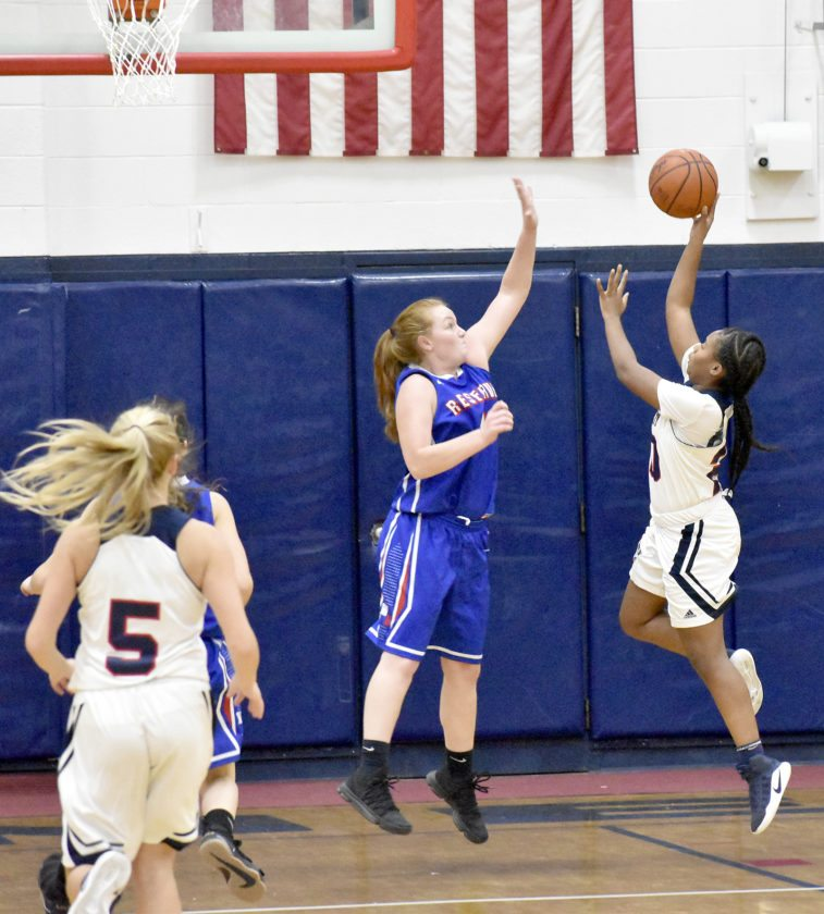 Danielle Bradley (far right) of John F. Kennedy goes up for a shot against Western Reserve's Alexis Hughes Thursday night at JFK.