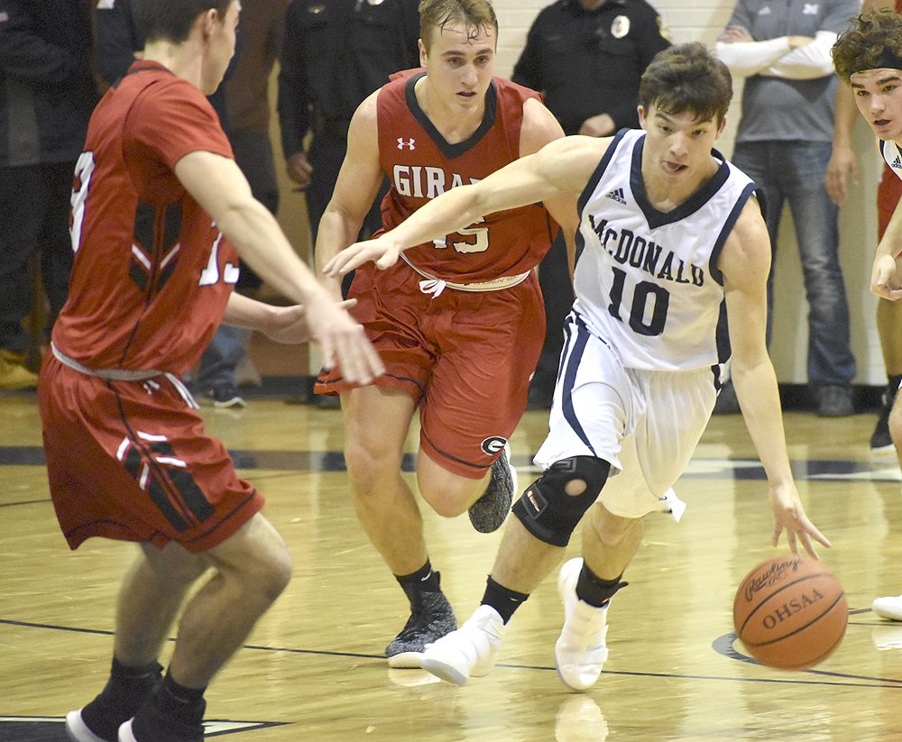 Tribune Chronicle / Joe Simon McDonald's Josh Celli (10) dribbles up court while being defended by Girard's Mark Waid, center, and Austin O'Hara, left.