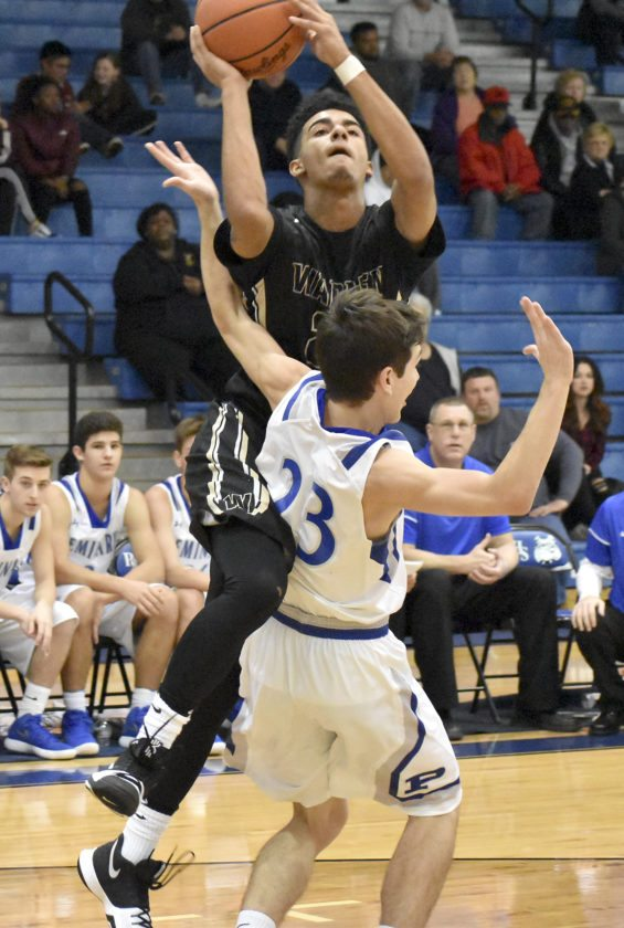 Tribune Chronicle / Marc Weems Warren G. Harding's Dom McGhee tries to score against the defense of Poland's Michael Cougras Tuesday night at Poland. The Bulldogs defeated the Raiders, 57-40.