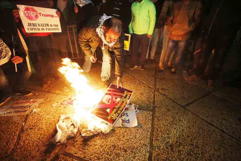 AP Palestinians burn a poster of U.S. President Donald Trump during a protest in Bethlehem, West Bank, Wednesday. Defying dire, worldwide warnings, Trump Wednesday broke with decades of U.S. and international policy by recognizing Jerusalem as Israel's capital.