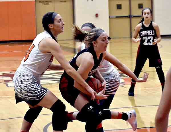 Tribune Chronicle / Marc Weems Canfield's Ashley Venerzo, center, drives by Howland's Kendyl Buckley, left, as Canfield's Jill Baker, right, looks on Wednesday in Howland.