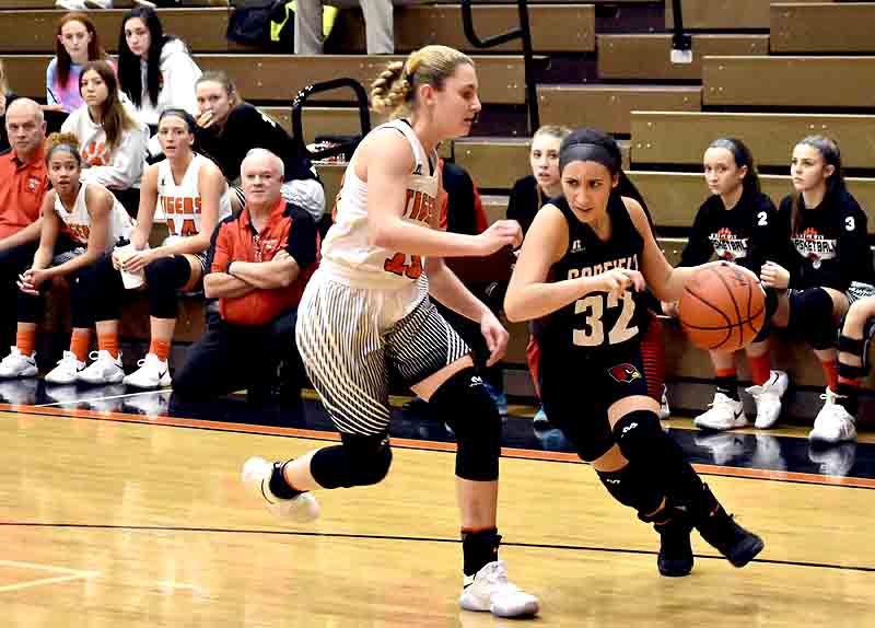 Tribune Chronicle / Marc Weems Howland's Gabby Hartzell, left, guards as Canfield's Christina Rivera, right, dribbles toward the baseline during Wednesday's game at Howland High School. The Cardinals beat the Tigers in double overtime, 68-65.