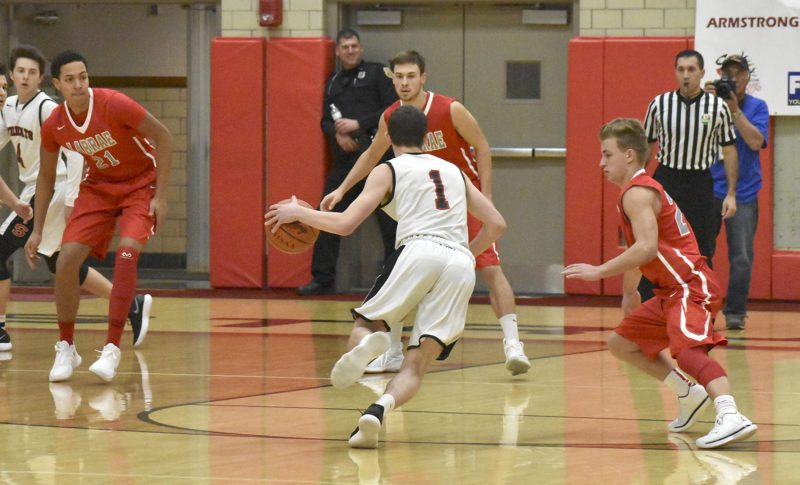LaBrae defenders, from left, Tyler Stephens, Aaron Iler and Benton Tennant converge on Isaiah Torrance (1) of Struthers Saturday night at Struthers.