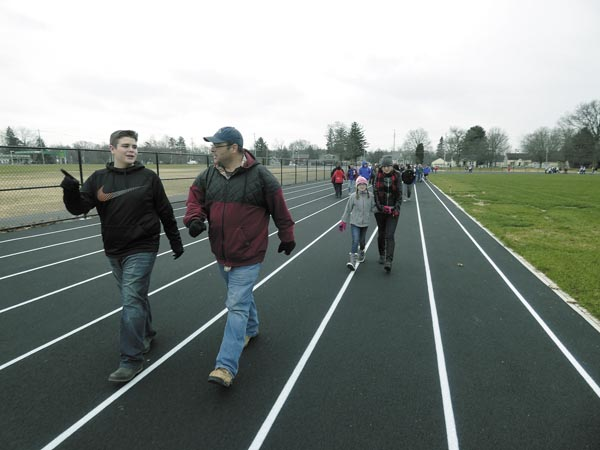Deane DeCiancio, far left, Mark Wise, second from left, Riley DeCiancio, second from right, and Melissa Oakman-Wise, far right, on Monday lead the first lap on the Lordstown Veterans Memorial Stadium. The track and soccer complex was funded through a contribution from the Lordstown Energy Center. The Wise family was able to walk the first lap in honor of Douglas Wise, a custodian in the district for about 7 1/2 years before he died in October. Tribune Chronicle photos / Raymond L. Smith
