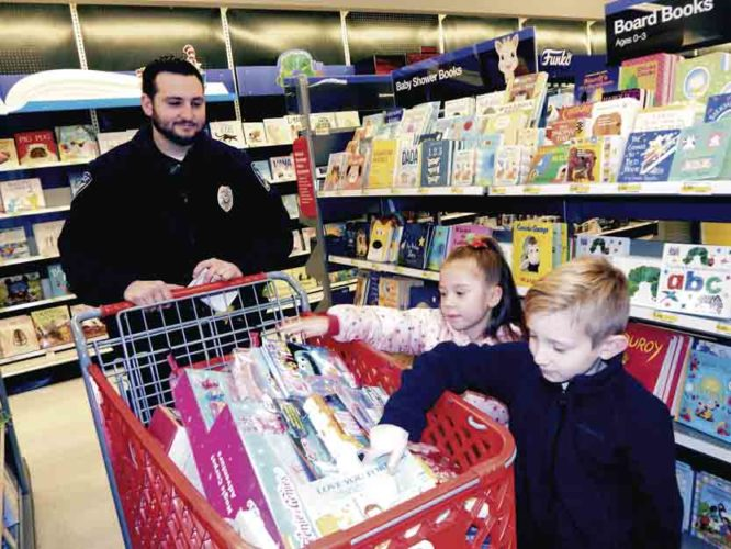 Tribune Chronicle / Bob Coupland Niles police officer Anthony Roberts, left, helps Jordan O'Brien, 5, center, and Jaxon Dye, 6, both of Niles, pick out Christmas gifts Tuesday at Target during the annual Shop with a Cop put on by the Niles Fraternal Order of Police Lodge 27. Each of the 15 kids who participated were given $100 to shop for gifts for themselves and others.