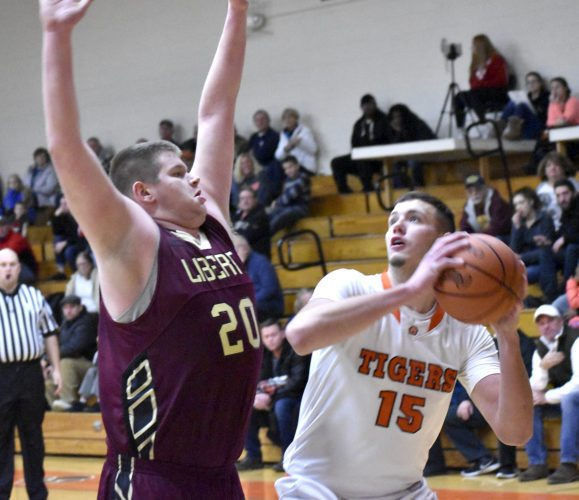 Tribune Chronicle / Marc Weems Gage Friend, right, of Newton Falls looks to score inside against Liberty defender Derek Gilcher Friday night during the Tigers' 64-20 win at home.