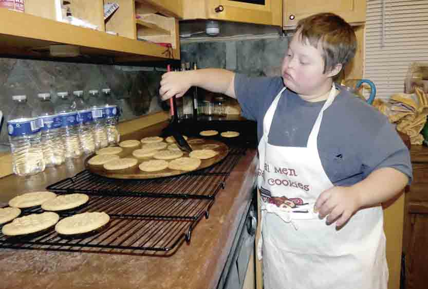 Tribune Chronicle / Burton Cole Donnie Eisenbraun, 11, of Southington, slides freshly baked peanut butter cookies from a cookie tray onto a cooling rack. He bakes for his business, Donnie's Cookie Jar, at the Putting Downs First home in Champion. His aunt, Cara Meadows, is executive director of the Putting Downs First organization.