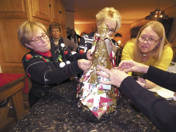 From left, Joan Bott of New Castle, Pa., Sandy Moss and Deb Moss, both of Niles, hang cookie ornaments on a tree at Theresa Kowalczyk's 12th annual Cookie Exchange Party at Kowalczyk's home in Fowler. The women donate the tree to someone in need of holiday cheer. Tribune Chronicle photos / Burton Cole
