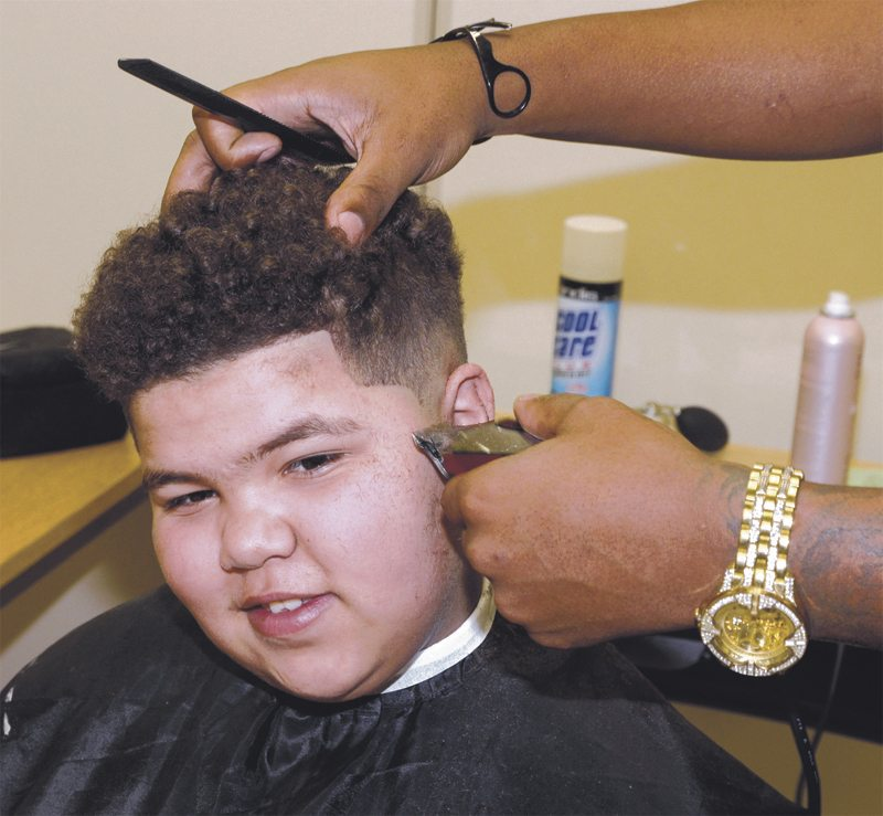 Tribune Chronicle / R. Michael Semple Emmanuel Washington, 13, a sixth-grader at Willard PK-8 School in Warren, gets a free haircut from barber Mike Dorsey of Warren Thursday morning at the school. Thirty-six students, boys and girls, received hair cuts from volunteers just in time for Christmas.
