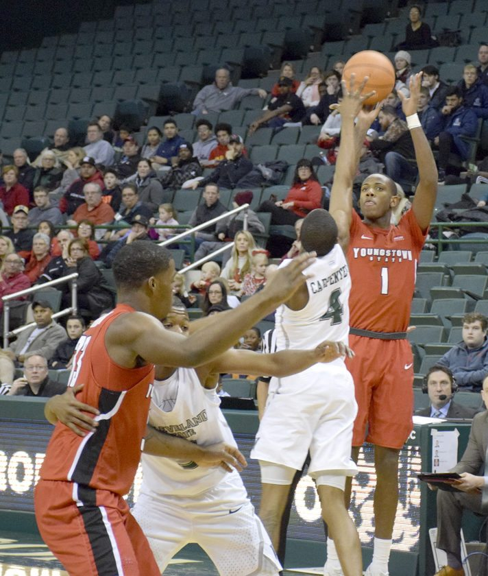 YSU's Braun Hartfield hit a 3 over Cleveland State's Kenny Carpenter in front of the Cleveland State bench during Monday's first half. Hartfield had three 3s in the first 20 minutes of a 80-77 win.