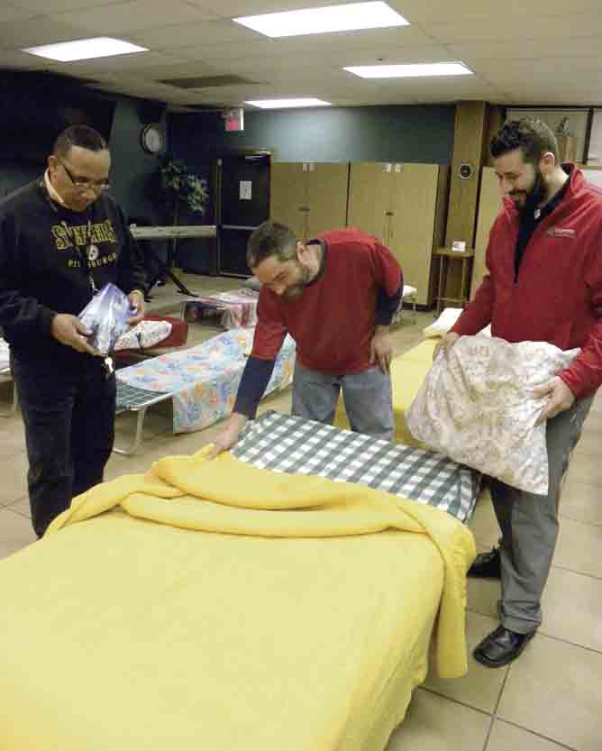 Tribune Chronicle / Lexy Cummins Reginald McCain, left, a staff member at the Warren Family Mission Men's Program, William Joyce, 38, center, of Niles, and Dominic Mararri, right, public relations director for the mission, prepare a bed Tuesday at the Men's Home at 1228 W. Market St. in Warren. The mission is expecting an influx of clients with this week's cold snap.