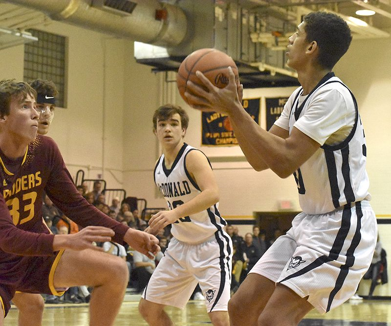 Tribune Chronicle / Marc Weems McDonald's Braeden Poole looks for a shot against South Range's Brady White (33) and Jaxon Anderson.